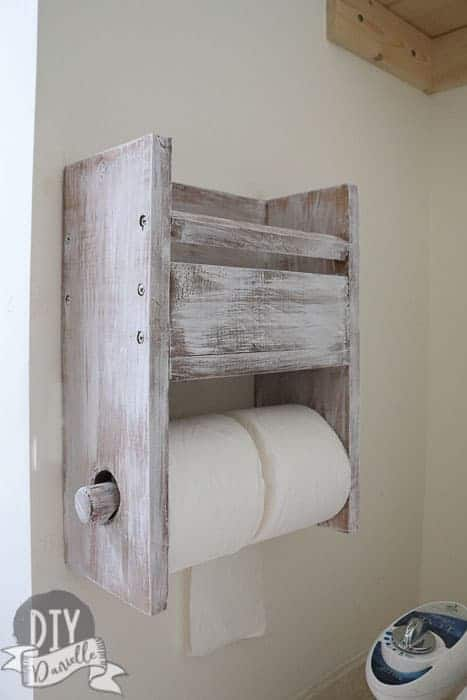 Rustic toilet paper holder that has room for two rolls, plus has storage above it for a magazine or family cloth.