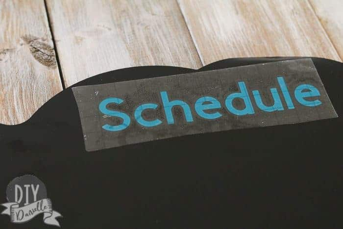 """Applying the word """"schedule"""" to the top of my chalkboard using Cricut transfer paper."""