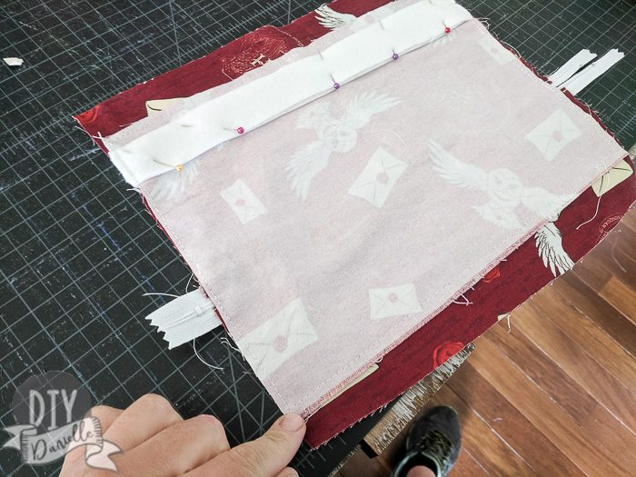 Sewing back and front fabrics right sides together. Also pin the stabilizer in place.