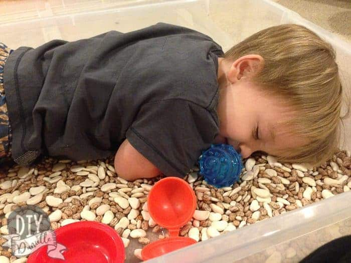 Son laying in a bean sensory bin.