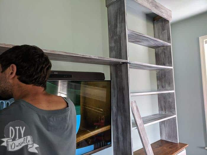 Middle shelf being added to the bookshelves. Two shelves will go over the TV. They're held in place with clamps while my husband screws them in via pocket holes.
