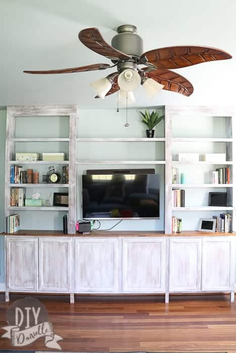 Photo of the bookshelves and cabinets from the front. The finish matches well with the flooring and ceiling fan.