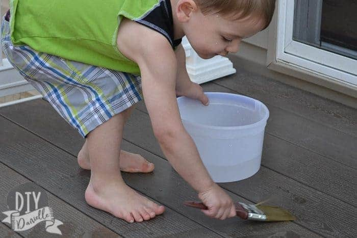 Boy painting the deck with paintbrush with water on it.