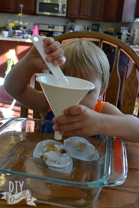 Toddler using a funnel and a measuring spoon to melt ice.