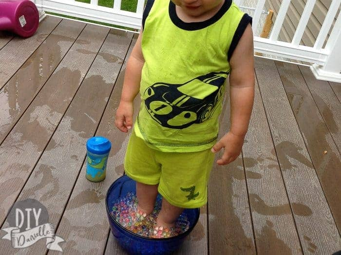 Son standing in a bowl of water beads.