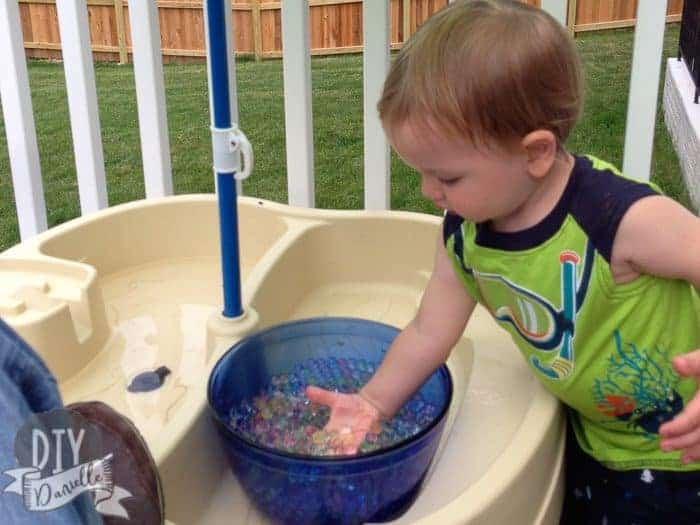 Toddler playing with water beads.