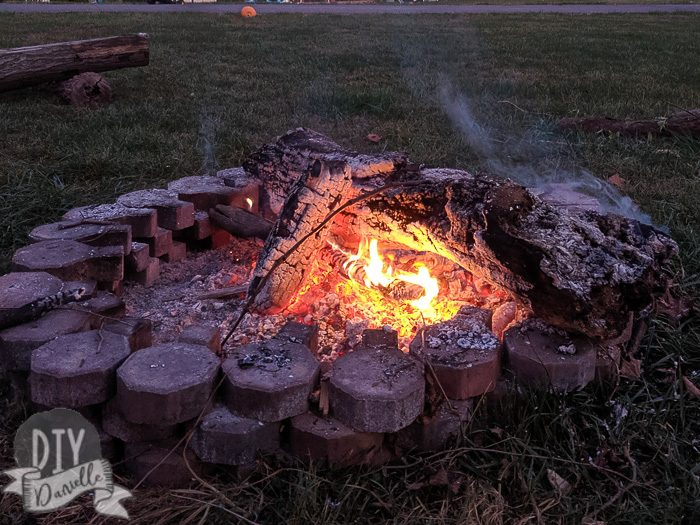 Fire pit made with pavers... with fire inside it and logs.