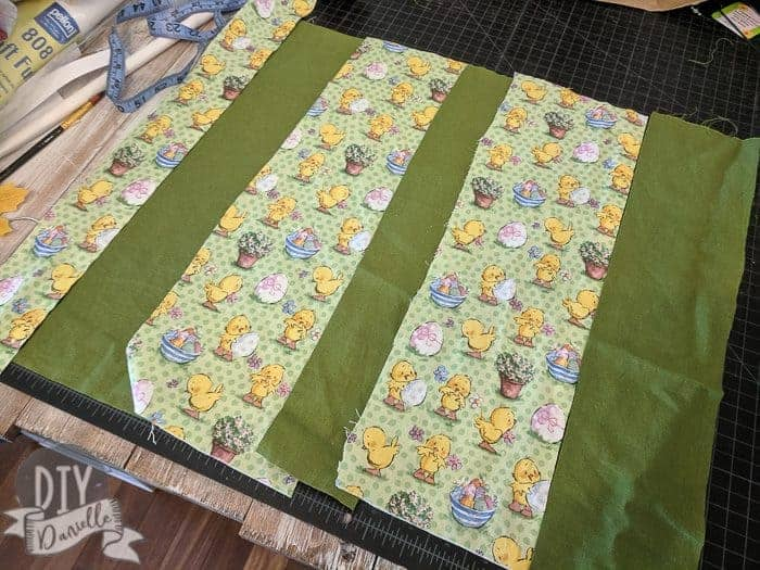 Piecing together Easter fabric with coordinating green fabric.