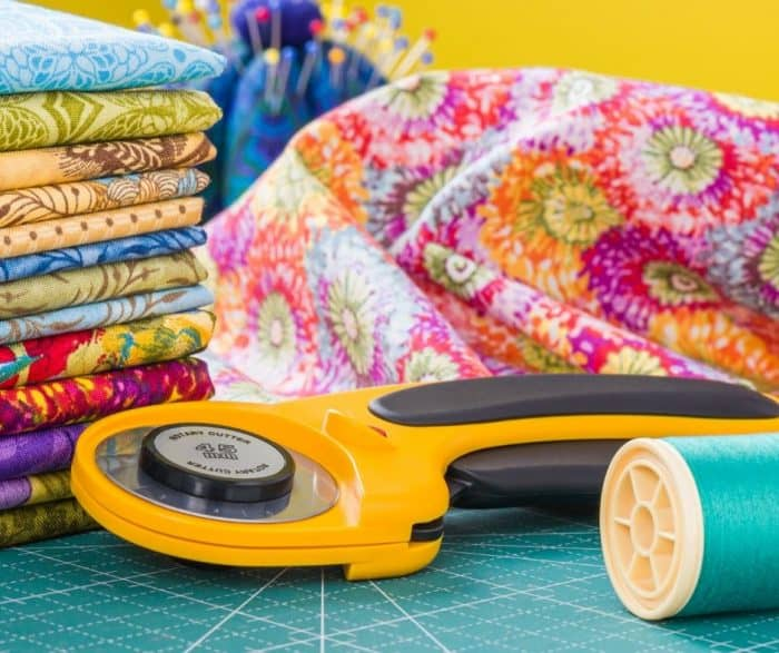 Photo of an orange rotary cutter next to thread and fabric.