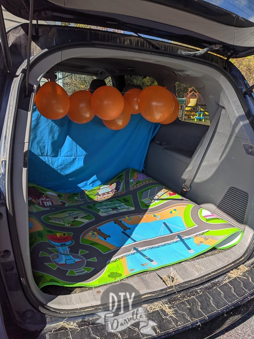 Setting up my trunk with backdrop, balloons, and a easy to clean mat.