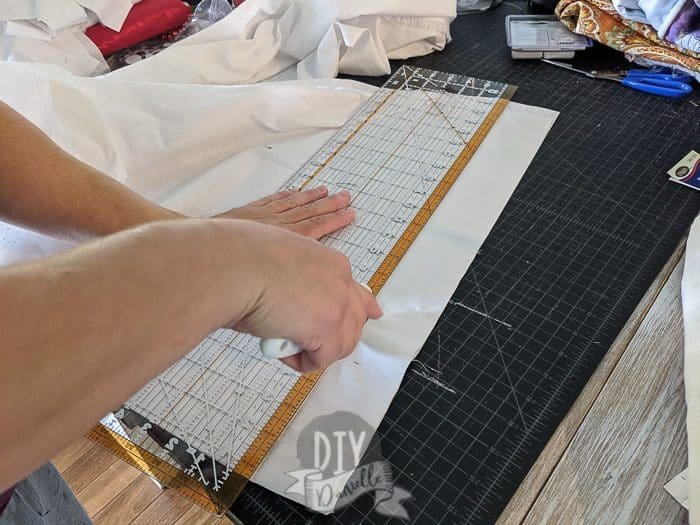 Using a rotary cutter to cut strips of white fabric. Also pictured: self healing cutting mat and quilting ruler.