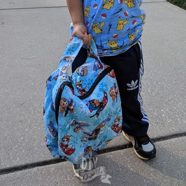 Zippered lunch bag with handle made with Paw Patrol fabric and held by toddler.