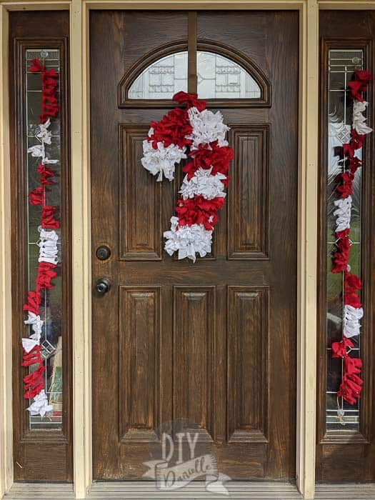 Twine and fabric banners on windows framing the wood door. Candy cane wreath on door.