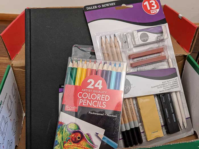 My son picked out some colored pencils, a drawing kit, and a sketchbook as art supplies to go in a box for a boy, 5-9 years old.