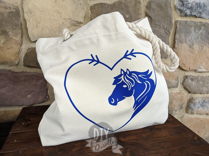 Outside of the canvas tote bag with rope handles. The iron on design is purple with a heart around a horse's head.