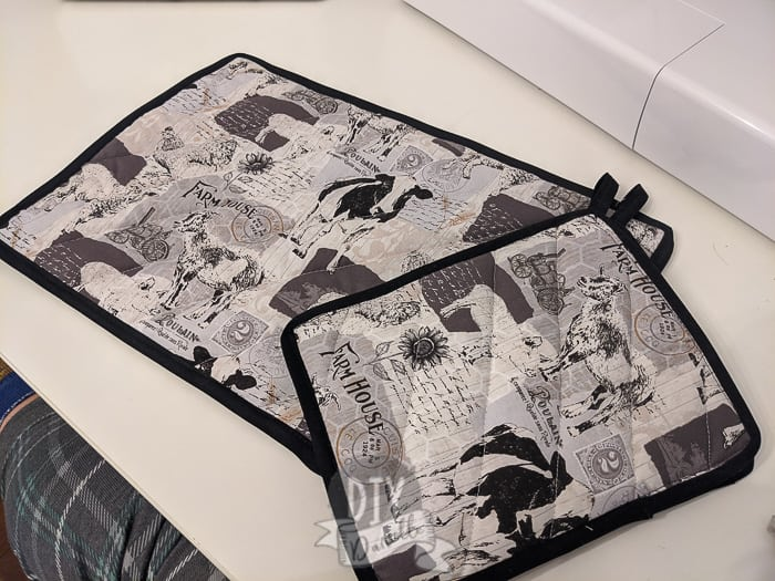 Double Fold Black bias tape around two pot holders with farmhouse fabric (farm animals on it).