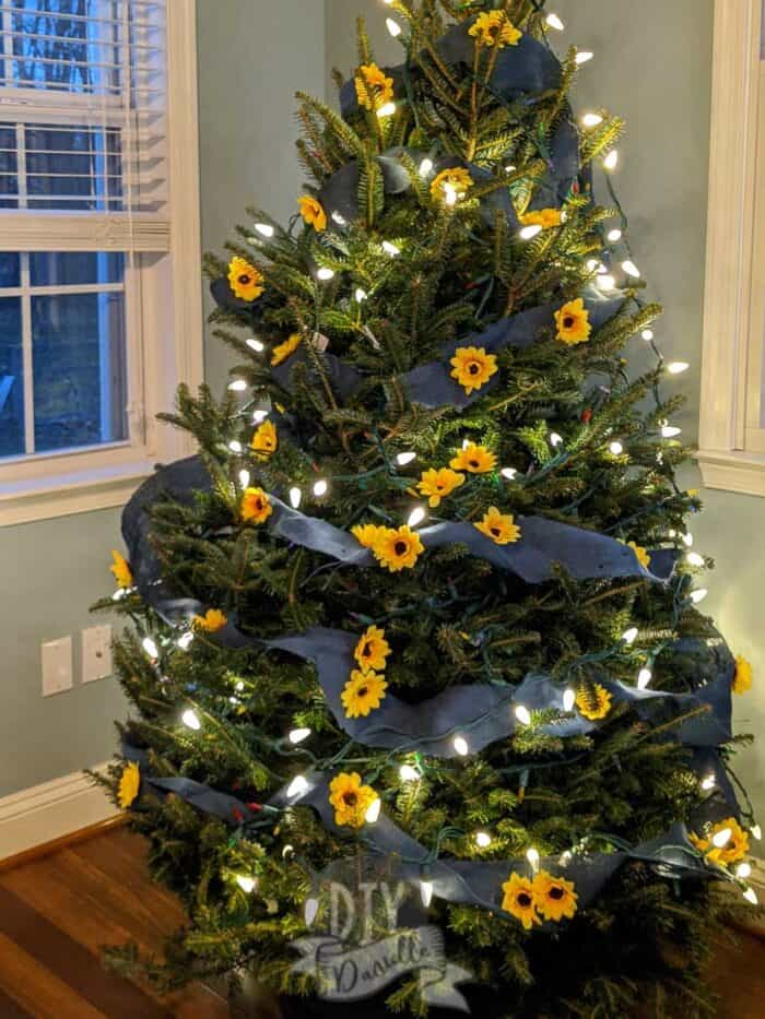 White lights on Christmas tree with sunflowers and blue burlap.