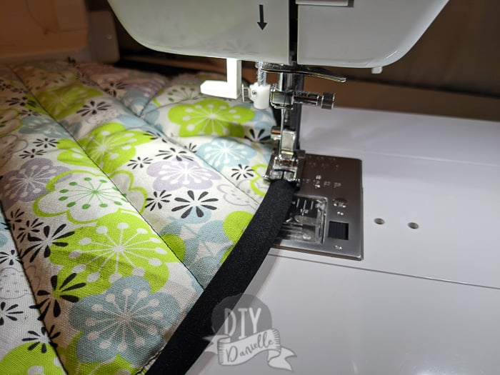 Sewing double fold bias tape on once folded over the fabric edge.