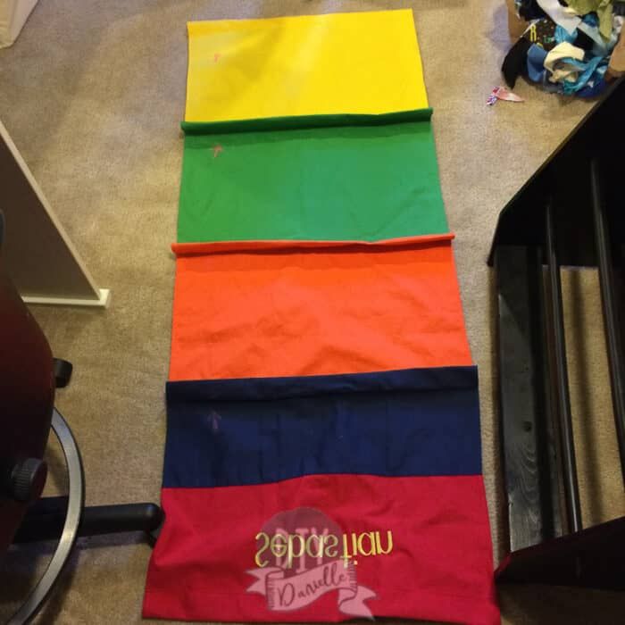 Old slings laid out as a template for the new ones. These were rainbow colored and said Sebastian.