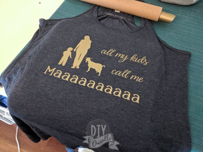 """All my kids call me maaaa"" with a woman, baby, and goat on a shirt."