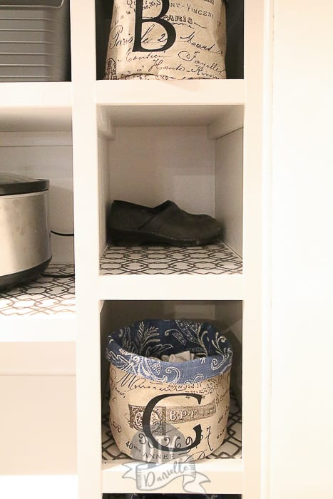 Shoe storage for the mudroom shelf. The baskets hold socks and have a letter for each person's first name. Shoes hide behind the basket.