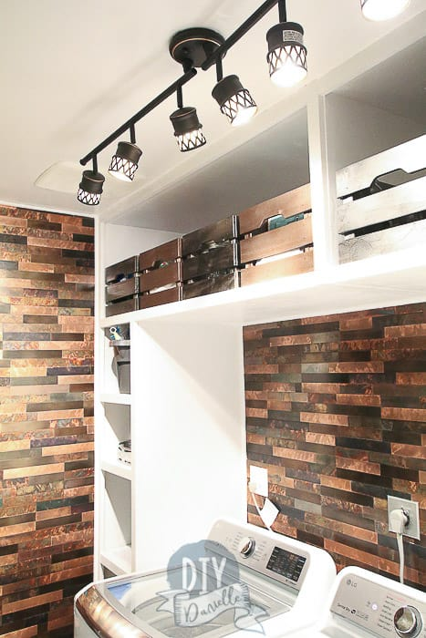 Close up of lighting, storage bins, and backsplash in this DIY mudroom and laundry room.