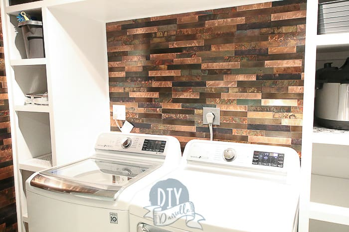 Aspect Backsplash in Metal and Aged Copper behind the washing machine and dryer. White shelves framing the wash area.