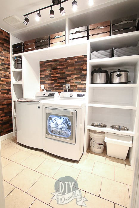 White DIY built in shelves for a laundry room with dog feeding station. Metallic backsplash.