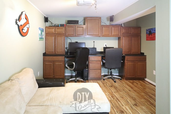 Cabinets used to create a built-in office area in a dark basement room.
