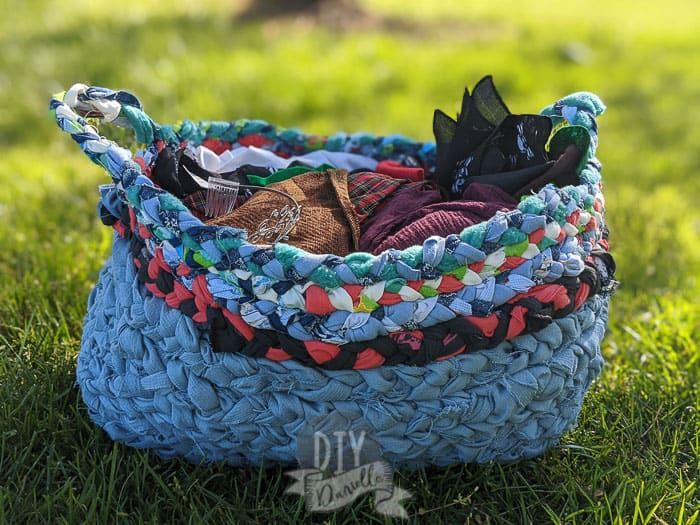 Storage basket made with upcycled fabric braided together. Two handles.