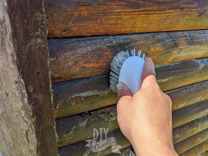 Using a scrub brush and DIY wood cleaner to get dirt and debris off the old wood of this log cabin playhouse.