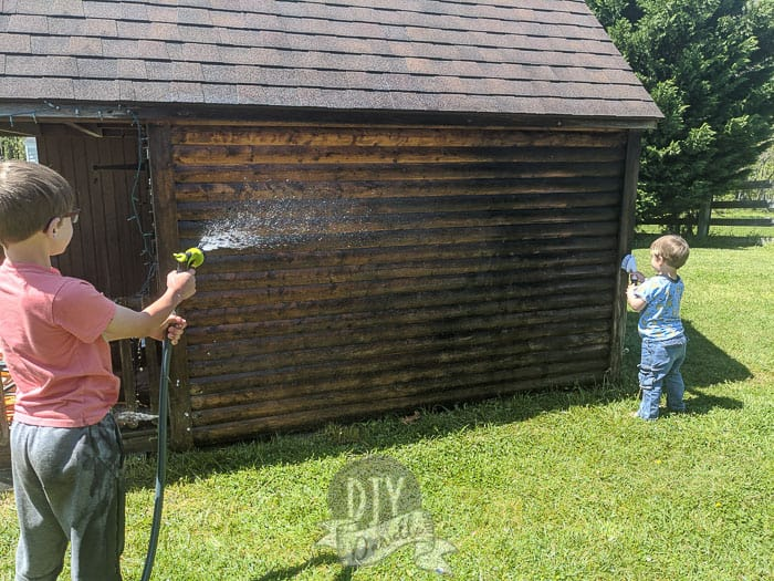 Kids helping clean the old wood log cabin.