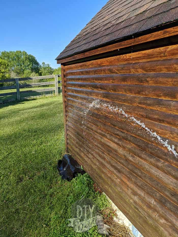 Rinsing soap and dirt off the sides of the playhouse.