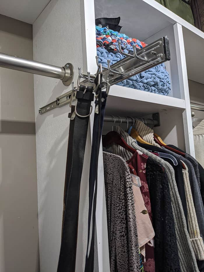 Silver/Chrome Belt rack that slides out from closet. It needs to be screwed into wood shelving or the wall. Four belts hanging from it.