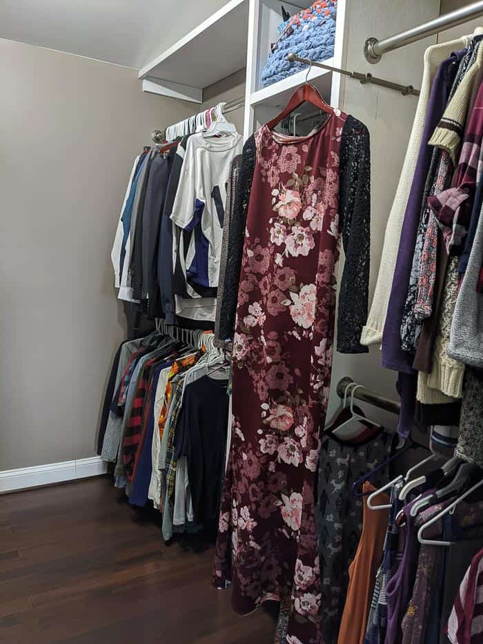 Silver/Chrome Valet rod that slides out from closet. It needs to be screwed into wood shelving or the wall. Floor length floral dress hanging from it.