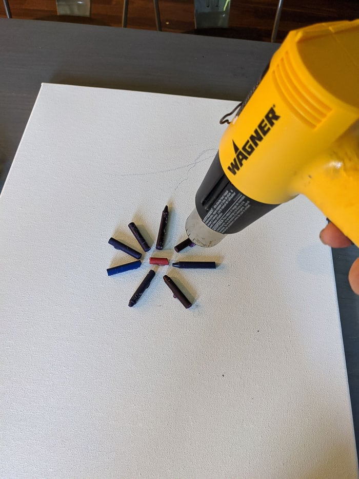 Using a Wagner Heat Gun to melt the crayons that have been glued to the canvas.