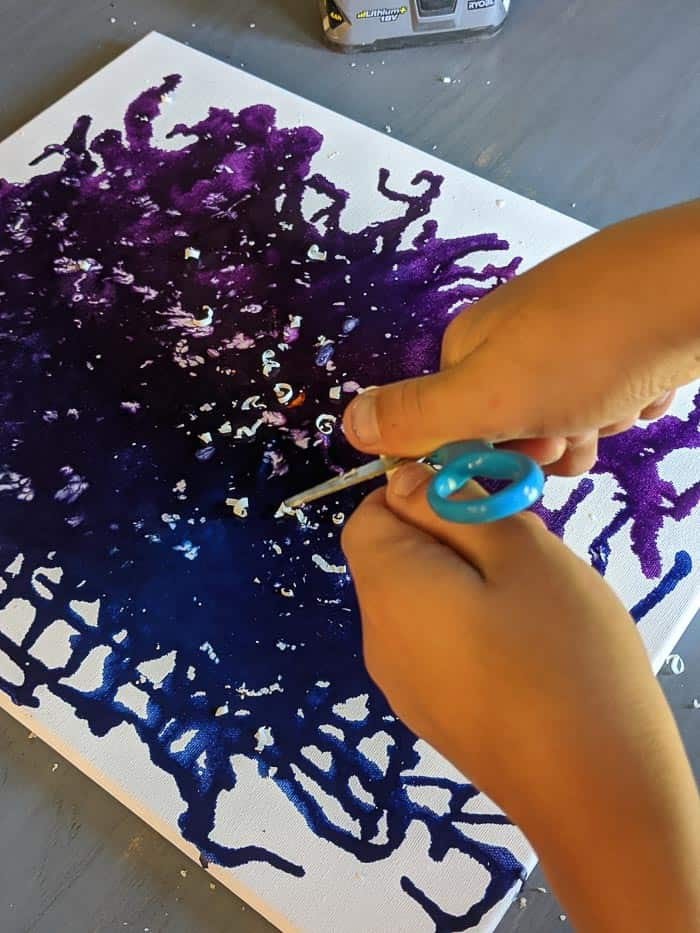 Using scissors to shave pieces of white crayon off onto the canvas.