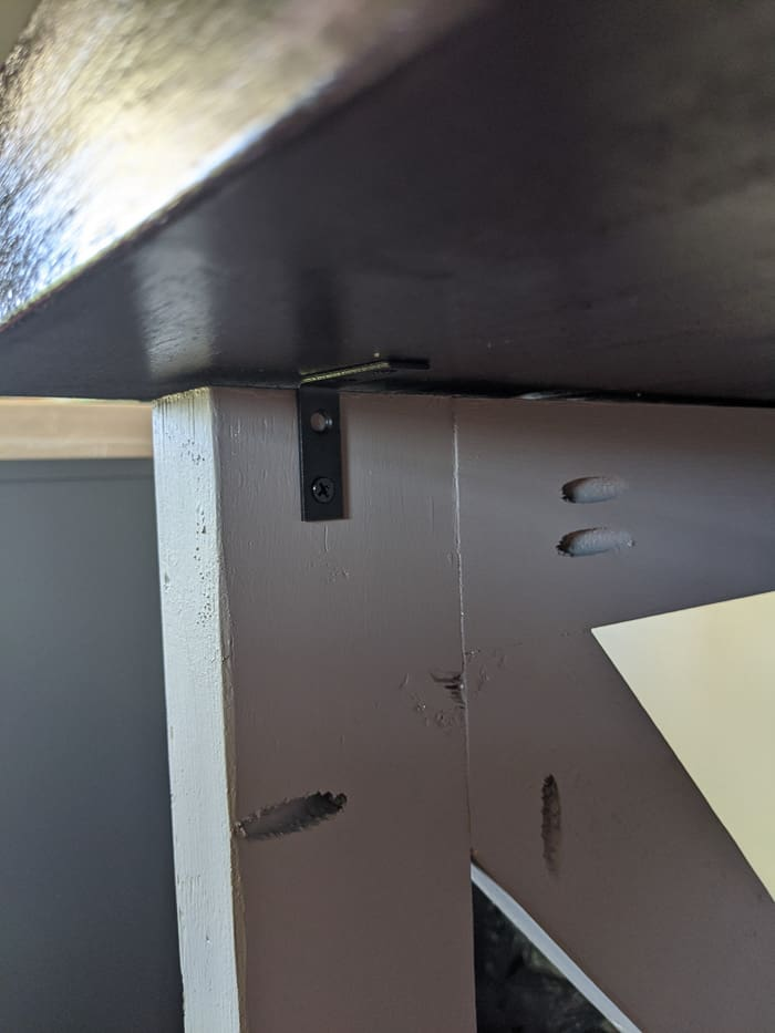 Corner braces hold the butcherblock to the legs of the desk.