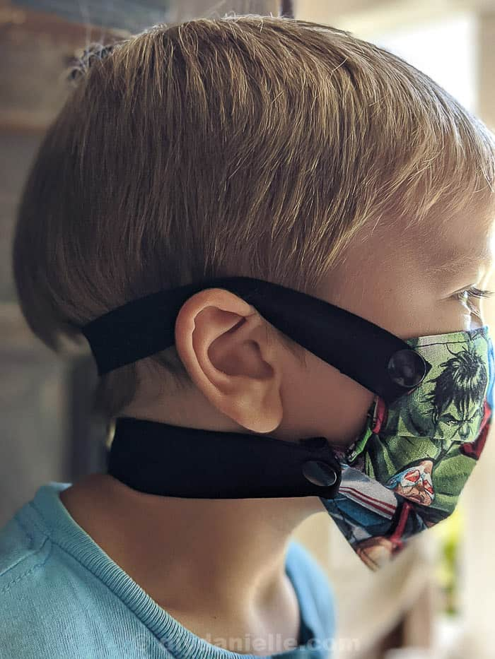 3 year old boy with blond hair wearing a super hero mask with elastic straps that snap on around the back of his head and neck.