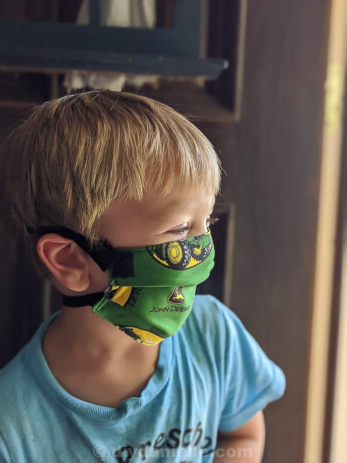 3 year old boy with blond hair wearing a John Deere mask with Velcro straps,