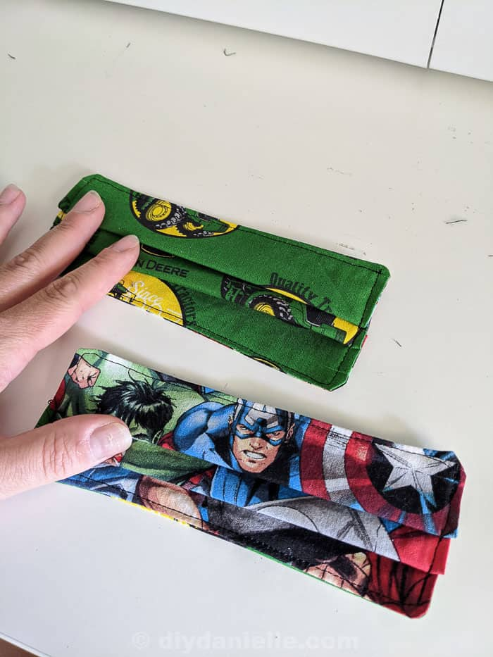 Pleats sewn down and the masks have been top stitched here- but they don't have straps yet. John Deere mask and super hero mask.