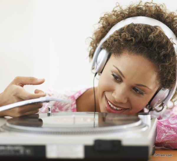 Young woman putting on vinyl record on record player