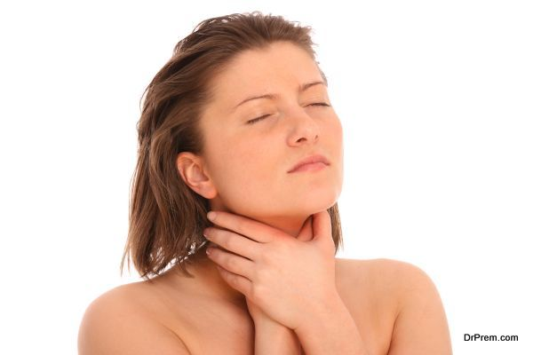 A picture of a young woman suffering from sore throat over white background