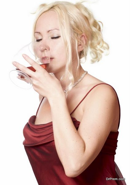 Woman wearing evening dress drinking brandy isolated on white