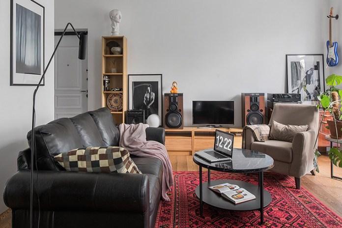 Apartamento urbano/industrial. Sala de estar com sofá preto e rack de madeira