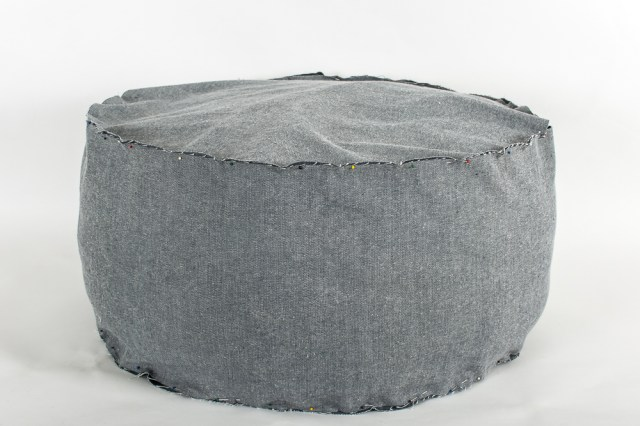 Re-cover a leather pouf with a fabric slipcover.