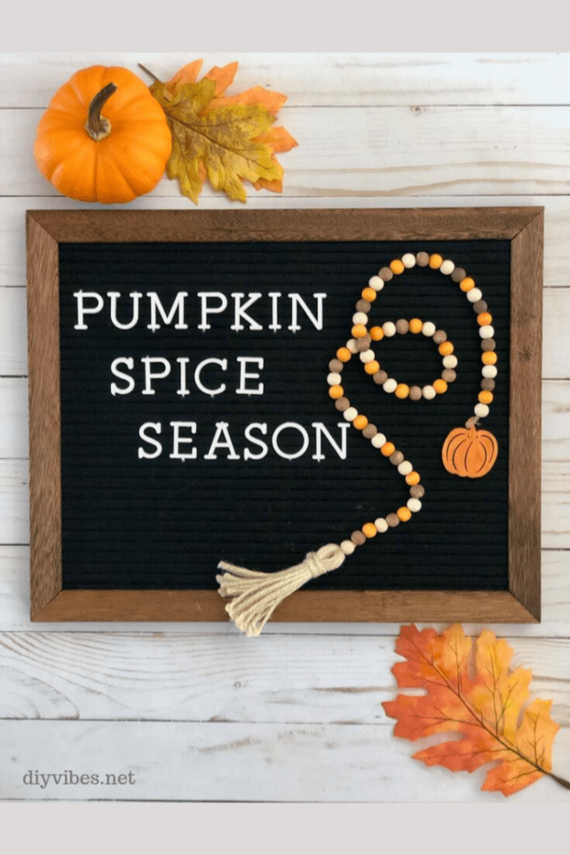 pumpkin spice sign with fall wood bead garland draped on it