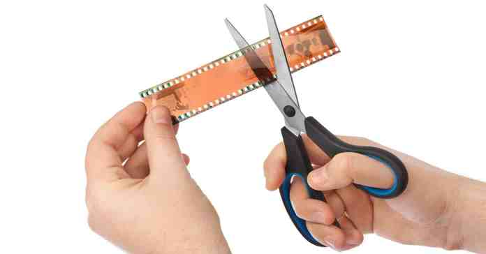 Hand holding a piece of film with the other hand using scissors to cut it.