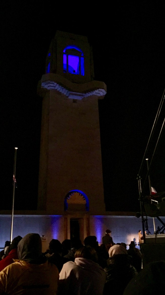 The Australian war memorial at Villers Bretonneux lit up. A crowd is in front and there is a stage with people on it.