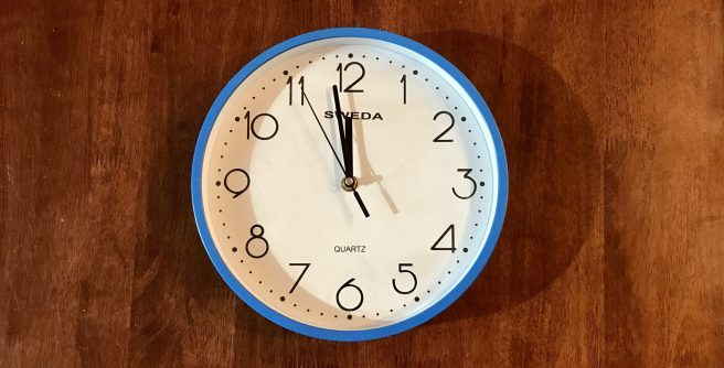 Analogue clock showing one minute to midnight